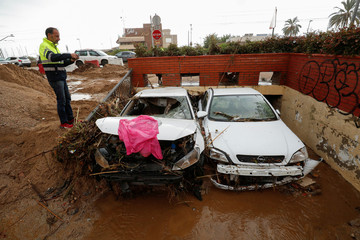 A man takes a picture of damaged cars after floods caused by torrential rains in Arenys de Mar