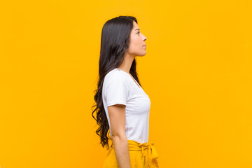 young pretty latin woman on profile view looking to copy space ahead, thinking, imagining or daydreaming against orange wall