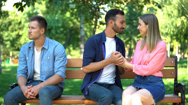 Unhappy young male sitting aside loving young couple on date, feeling lonely