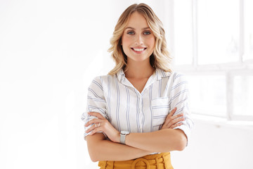 Image of attractive elegant blonde woman standing in white office