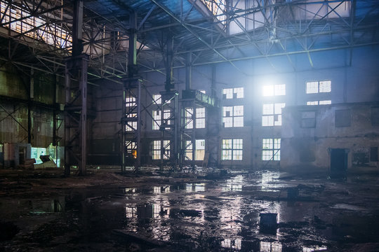Dark dirty flooded dirty abandoned ruined industrial building with water reflections at night