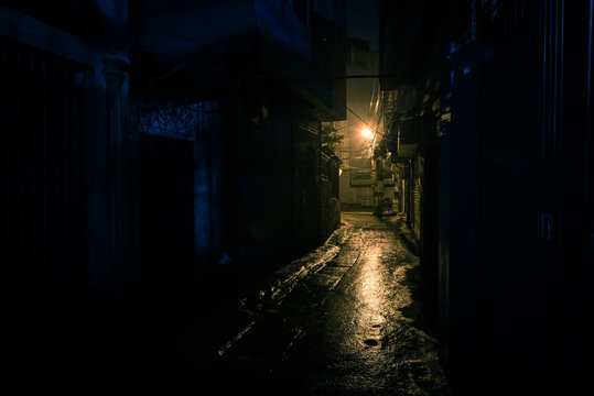 Empty and dangerous looking urban back-alley at night time in suburbs Hanoi