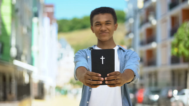 Happy african-american boy showing holy bible on camera and smiling, religion