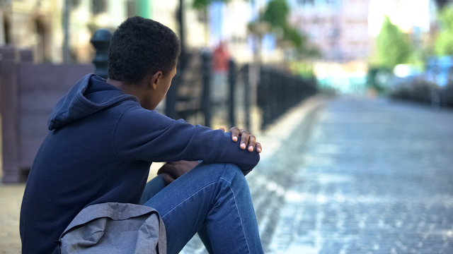 Sad mixed-race teenager sitting on sidewalk, relationship problems, awkward age