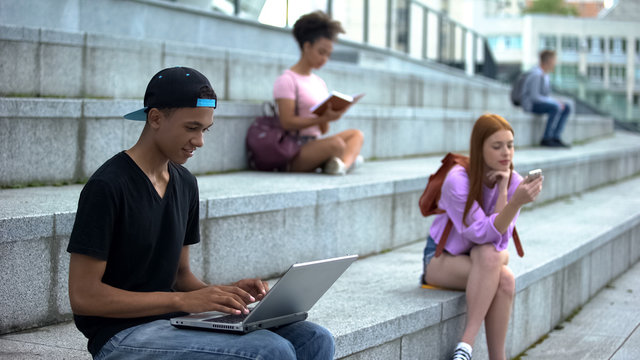 Young student typing laptop sitting campus stairs, digital generation, freelance