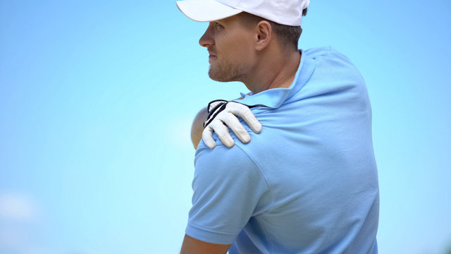 Athletic male golfer suffering terrible pain in shoulder, sport and health