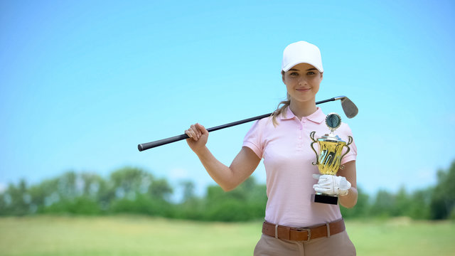 Happy female golf player with club and gold cup smiling on camera, sport victory