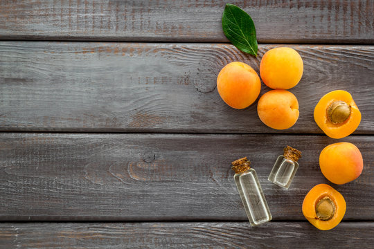Fruit aroma oil. Apricot kernel oil on dark wooden background top view frame copy space
