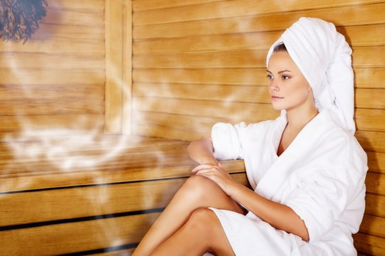 Young beautiful relaxed woman in sauna