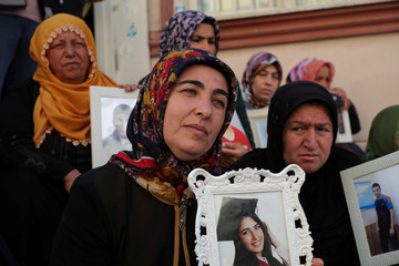Mothers hold pictures of their children who joined the PKK militant group, during a sit-in protest outside the local headquarters of Pro-Kurdish HDP in Diyarbakir