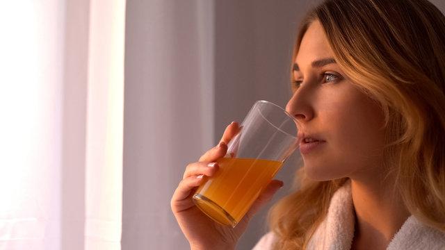 Girl in robe drinks orange juice looking in window, vitamins for skin, face care