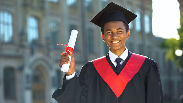 Joyful college student showing diploma celebrating graduation day, achievement