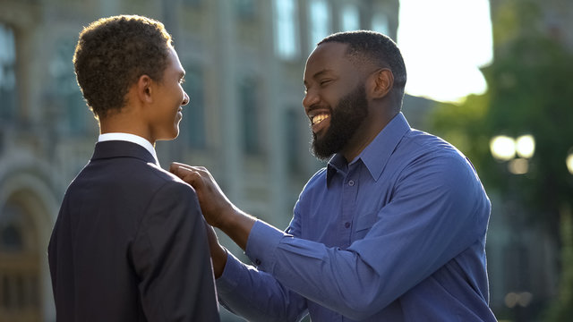Excited african man feeling proud of young son in prom suit, college graduation