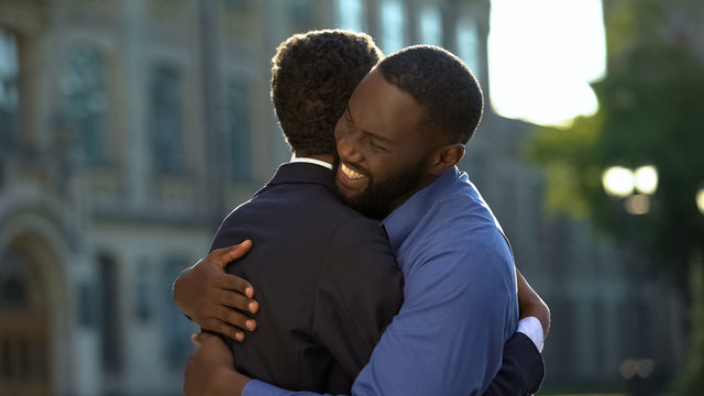 Cheerful black father embracing young son in prom suit, college graduation, joy