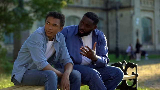Black teenager male ignoring scolding dad sitting on campus bench, conflict