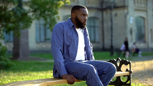 Upset african american male sitting alone on college bench stress after conflict
