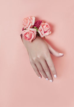 Hand with paper flowers and painted nails is thrust through a hole in the paper background. Cosmetics and hand care, moisturizing and wrinkle reduction