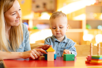 Cute woman and kid playing educational toys at kindergarten or nursery room