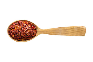 Fototapete - chili pepper flakes in wooden spoon isolated on white background. spice for cooking food, top view.