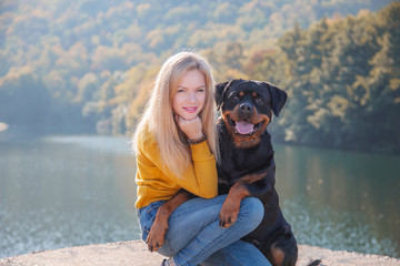 Young attractive blonde woman and her German Rottweiler dog sitting on background of beautiful autumn landscape. Friendship, pet and woman Papier Peint