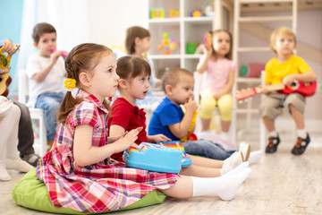 Group of kids 3-4 years old playing toy musical instruments. Early music education in kindergarten