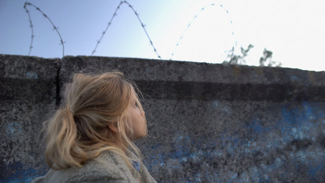 Little refugee girl looking at barbed wire, dreaming of new homeland, migration