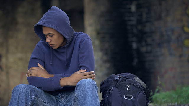 Injured male child sitting on street near backpack, feeling cold, escaping home