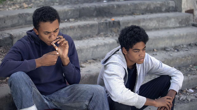 Desperate african teenagers thinking of family problem, smoking cigarette