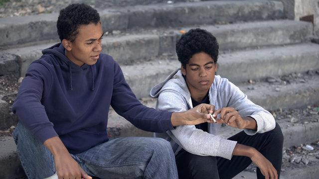Two black teenagers smoking marijuana weed stairs, street lifestyle, addiction