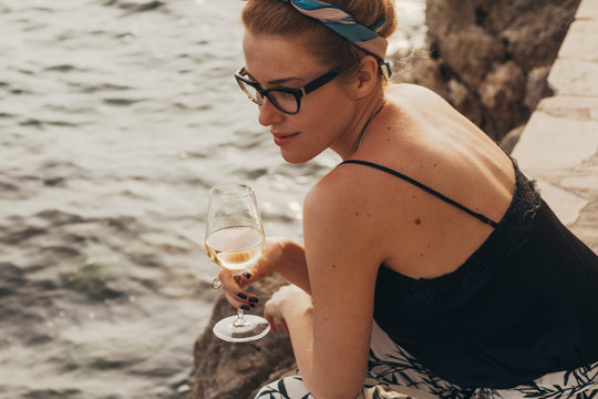 Beautiful stylish woman daydreaming while siting on the seacoast and holding glass of wine.