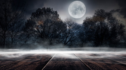 Dark forest. Gloomy dark scene with trees, big moon, moonlight. Smoke, shadow. Abstract dark, cold street background. Night view. Night wooden table