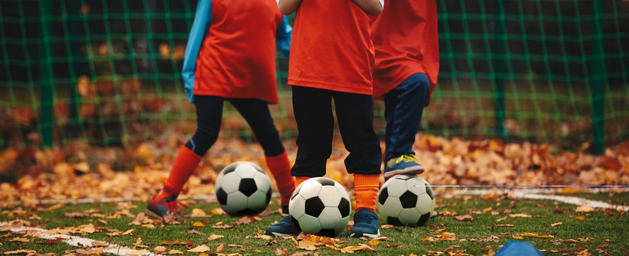 Three boys on soccer training in autumn time. Fall soccer outdoor practice session. Soccer players with ball on grass field covered with autumn leaves.