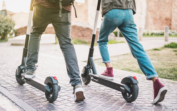 Close up of people couple using electric scooter in city park - Millenial students riding new modern ecological mean of transport - Green eco energy concept with zero emission - Warm sunshine filter