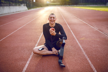 Fotomurales - Handsome smiling caucasian sporty handicapped young man in sportswear and with artificial leg sitting on racetrack, listening music and eating apple.
