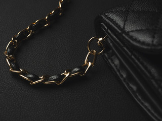 Close-up of gold chain of elegance women's accessories fashion black shoulder leather bag.