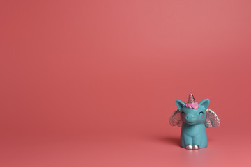 A blue unicorn with  silver wings  and pink hair on a pink background. A magical children 's toy isolated. Banner, postcard, copy space.