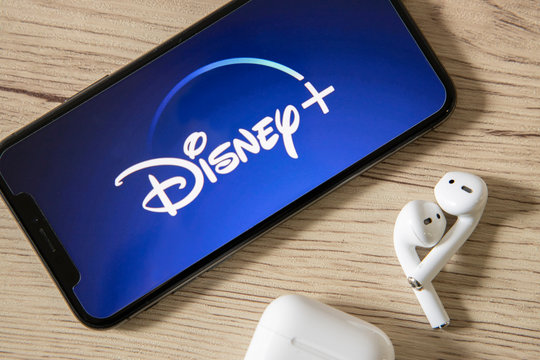 BANKKOK,THAILAND,OCTOBER 23: Iphone with Disney Plus Logo on the Screen on the Wooden Table on October 23,2019