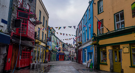 Foto auf Acrylglas Schmale Gasse View of the main high street in Galway City with the brightly painted buildings and cobblestone streets on a cloudy day
