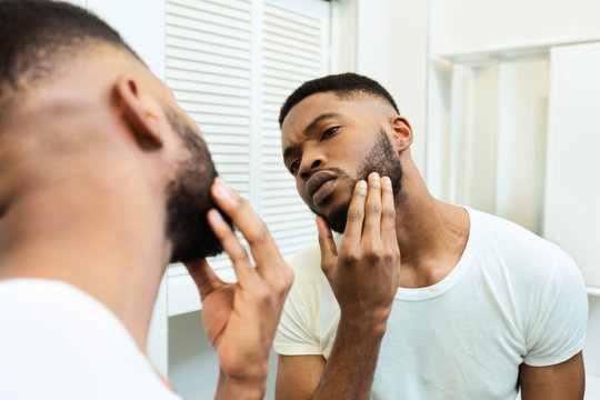 Concentrated african guy looking at his beard at bathroom mirror