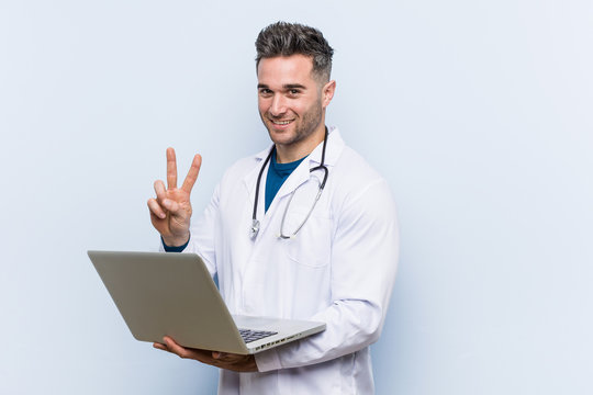 Caucasian doctor man holding a laptop showing victory sign and smiling broadly.