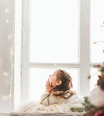 Cute little girl sitting on windowsill on Christmas.