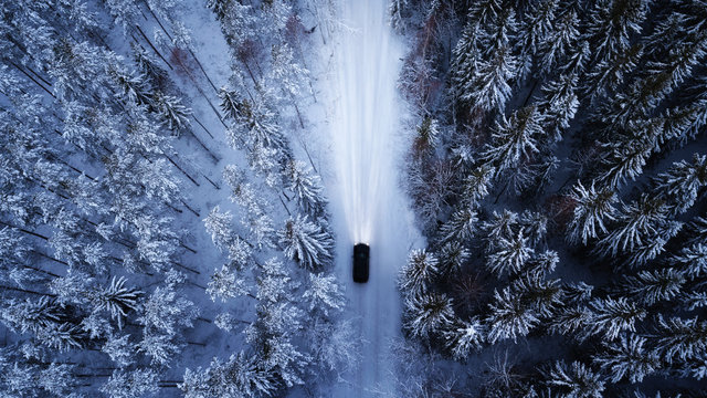 Aerial view of a car on winter road in the forest.  Aerial photography of snowy forest with car on the road.  Aerial photo. Car in motion