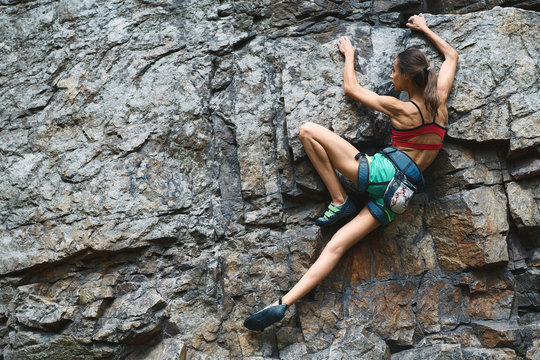 Sports Woman With slim fit body Climbing The Rock Having Workout In Mountains. rock climbing hard moves