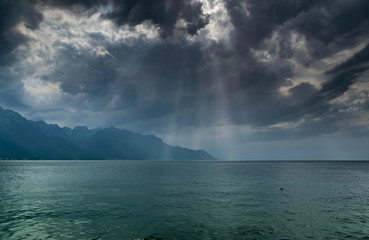 Landscape of Alps mountains,lake Geneva,dark clouds with sun rays before the rain.Shot taken from the shore of the lake in Montreux, Switzerland.