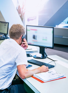 Car dealer sales manager talking with client on the phone and looking at computer. Back view