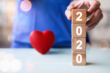 Doctor hand arranging wood block stacking with icon 2020 new year healthcare medical, insurance for your health.
