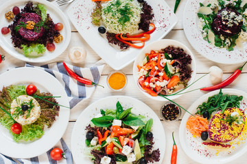 Festive banquet table. Top view of vegetable salads assortment on white wooden background.