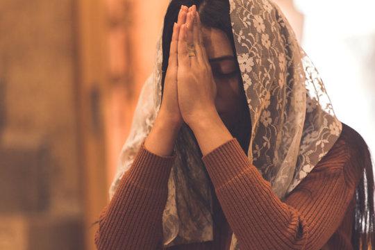 young sad woman praying in church