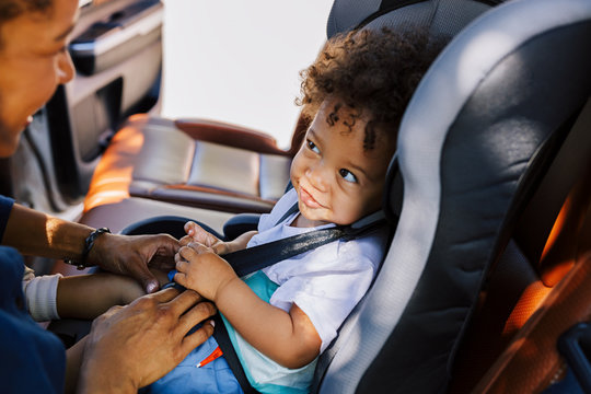 Smiling baby boy looking at his mother while sitting fastened in a car seat