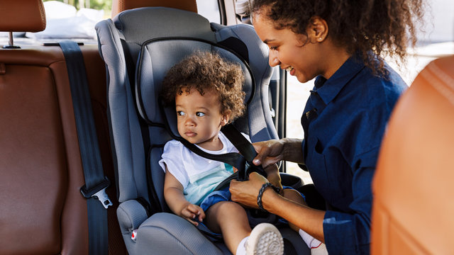 Little boy sitting in a baby seat looking away while mother fastening him